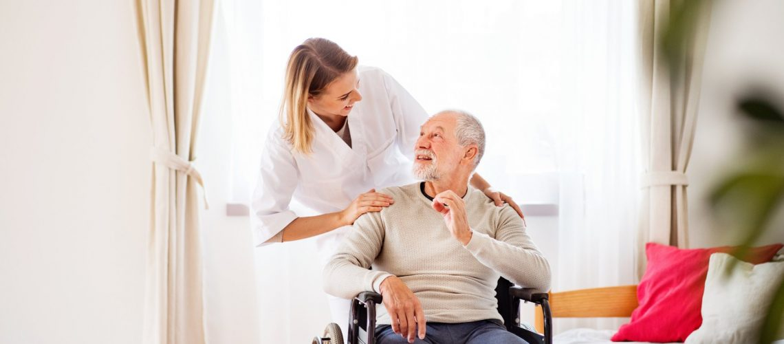 Health visitor and a senior man in a wheelchair during home visit. A nurse or a physiotherapist talking to a man.